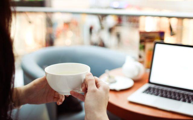 Eine Frau sitzt gemütlich mit einer Tasse in der Hand vor dem Laptop