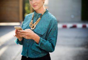 Bildverwendung zur Smartphone-Nutzung im Business-Kontext. Eine Frau mit türkisfarbener Bluse und Holzkette bedient ein Smartphone. Der Hintergrund ist verschwommen.